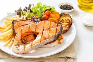 Double grilled salmon steak fillet with vegetable and french fries photo