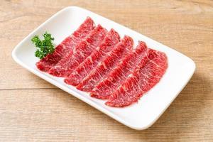 Carne fresca cruda en rodajas con textura de mármol servida para sukiyaki y shabu o yakiniku foto