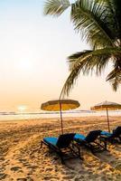 Silla de playa sombrilla con palmera y playa al amanecer - concepto de vacaciones y vacaciones foto