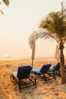 Umbrella beach chair with palm tree and sea beach at sunrise time - vacation and holiday concept photo