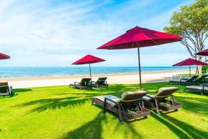 Sillas de playa y sombrillas con fondo de playa de mar océano foto