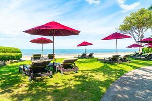 Beach chairs and umbrellas with ocean sea beach background photo
