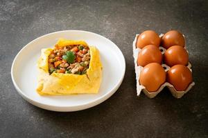 Egg wrap or stuffed egg with minced pork, carrot, tomato, and green peas photo