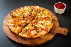 Seafood of shrimp, octopus, mussel, and crab pizza on wood tray photo