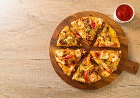 Mariscos de camarones, pulpo, mejillones y pizza de cangrejo en bandeja de madera foto