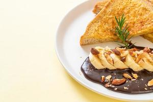 French toast with banana, chocolate, and almonds for breakfast photo