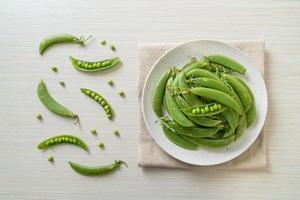 Guisantes verdes dulces frescos en la placa blanca. foto