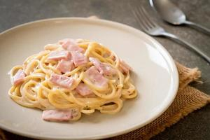 Espaguetis caseros con salsa de crema blanca con jamón - estilo de comida italiana foto