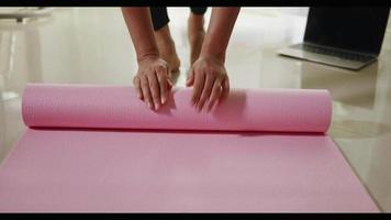 Woman yoga at home, female rolling up exercise pink yoga mat after exercising on floor in living room, Healthy sport fit lifestyle video