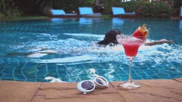Asian beautiful young woman enjoying swimming on pool relaxing with a glass of cocktail juice on side of the pool Selective focus at cocktail, Summer holiday vacation concept video
