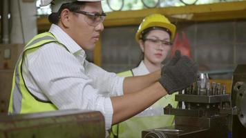ingénieur mécanicien professionnel asiatique et équipe d'exploitation portant un uniforme de travail de sécurité usine de fabrication industrielle de tour à métaux, ouvrier de tour de l'industrie lourde homme et femme video
