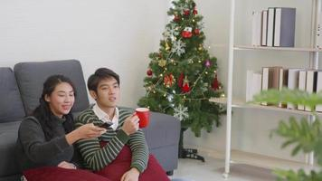 Happy Asian beautiful young family couple husband and wife enjoying in living room winter at home watching TV television entertainment or movie together video