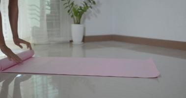 Young man yoga at home, male rolling up exercise pink yoga mat after exercising on floor in living room, Healthy sport fit lifestyle video