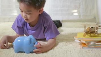 Happy Asian kid boy preschool putting pin money coins into blue faced piglet slot. Little child putting coin into piggy bank for saving with pile of coins at home, Investment education concept video