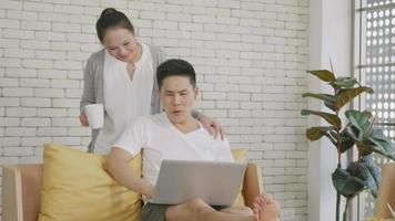 Happy Asian beautiful family couple husband and wife laughing sitting on sofa in the living room working with laptop computer at home. Woman brings coffee to the man during work video