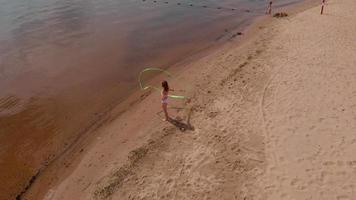 Aerial view of a young woman in a white body on a sandy beach dancing with a gymnastic ribbon video