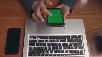femme d'affaires travaillant avec un ordinateur portable et elle vérifie un message sur l'écran vert du smartphone au café, une femme d'affaires recherche des informations sur des sites Internet et glisse sur un écran noir video