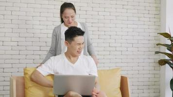 Happy Asian family couple husband and wife laughing sitting on sofa using laptop computer working from home Business man sitting on sofa home working on laptop her woman is giving her shoulder massage video