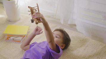 feliz niño asiático niño piloto de avión deseo del niño volar alto en casa en la alfombra. niño divertido que juega con un avión de madera de pasajeros de juguete y sueña con convertirse en piloto. vista superior video
