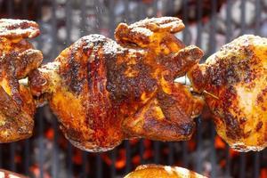 Pollos asados en asador a la parrilla sobre el fuego de una gran barbacoa foto