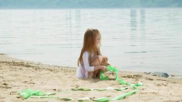 A preschool girl with a gymnastic ribbon on a sandy beach video