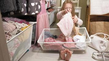 niña juega con ropa dentro de un armario video