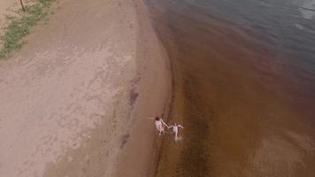 Aerial shot of mother and daughter running along the river video