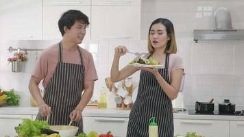 Happy Asian beautiful family couple husband and wife singing in kitchenware microphones in kitchen together having fun dance listen music at home, eat with dance at the same time. Two people dancing video