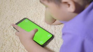 Asian kid boy preschool with gadget playing video games digital on mobile phone at home. Little child using and holding a smartphone green screen in hand, Technology generation concept