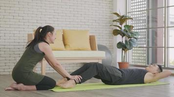 Happy Asian family couple husband and wife healthy trainer workout home in the living room. Fit man lifestyle doing sit up fitness exercise at home on floor with girlfriend support helping boyfriend video