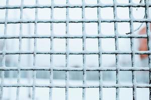 Ice-covered metal grill in winter - moisture condensation in the cold photo