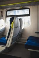 Interior of an empty train carriage - soft armchairs and large bright windows photo