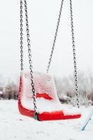 Columpio para bebés cubierto de nieve en invierno - parque infantil vacío - columpio de plástico rojo en el frío foto
