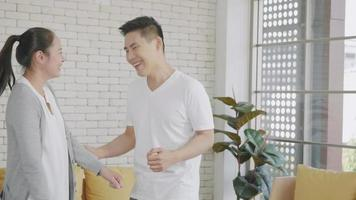 Happy Asian beautiful lifestyle family couple husband and wife laughing funny dancing enjoying weekend together in living room at home. woman and handsome man are enjoying spending time. Slow motion video