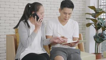 Happy Asian family couple husband and wife working confirming booking having talking call phone conversation and making writing notes of information together from home in living room. slow motion video