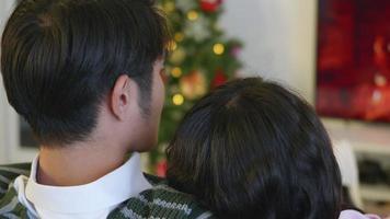 glückliches asiatisches schönes junges Familienpaar Mann und Frau sitzen auf dem Sofa vor dem Kamin im warmen Zuhause Weihnachten Winter umarmt Wohnzimmer, Rückansicht, Zeitlupe video