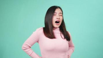 close up retrato joven bella mujer asiática aburrido bostezo cansado cubriendo la boca con la mano. Mujer inquieta sueño y somnolencia aislado sobre fondo azul. video