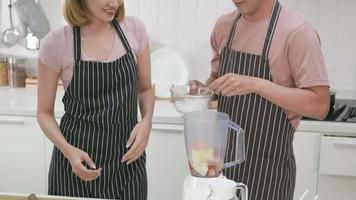 heureux asiatique beau jeune couple mari et femme faisant un smoothie aux pommes frais dans la cuisine ensemble à la maison. l'homme et la femme versent de la glace dans un mélangeur à jus. concept de mode de vie sain video