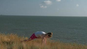 Young woman doing yoga outdoors video
