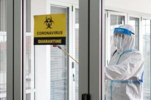 Worker from decontamination services wearing personal protective equipment or ppe including suit, face shield and mask. He uses disinfectant to spray and clean scientist lab photo