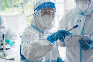 científicos en equipo de protección personal o ppe que investigan y experimentan para encontrar medicamentos para tratar la infección por covid-19 o coronavirus en el laboratorio foto