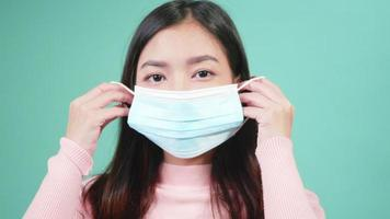Close up portrait young Asian happy beautiful woman wearing anti virus protection face mask. Female wear sterile medical mask, Coronavirus outbreak protection healthcare concept video
