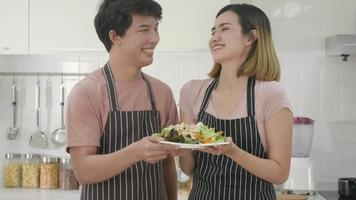 Happy Asian beautiful family couple husband and wife cooking vegetable salad in kitchen together at home. The man and woman handing a plate of salad to the camera. healthy food concept, slow motion video