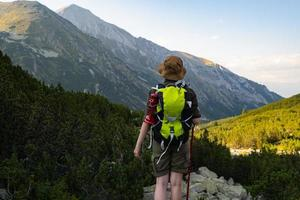 Young woman traveler with backpack in the mountains photo