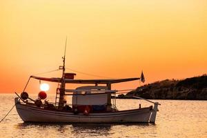 Landscape with fishing boat in the sea with beautiful sunrise on background photo