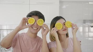 Happy Asian beautiful young family couple husband and wife enjoying smile and laugh holds a cut orange in front of the guy's eyes spending time together in kitchen at home. Slow motion video