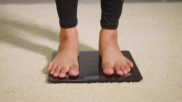 Asian young woman leg stepping standing on floor electric scales, female working out at home in living room, female stand on digital weighing machine. Healthy weight loss control concept video