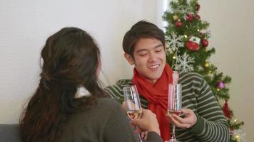 Happy Asian beautiful young family couple husband and wife on sofa in home living room, man and woman sit sofa in love clink glasses with champagne enjoy and drink winter holidays together slow motion video