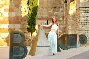 Young smiling woman walking on streets of Barcelona, stone background, noisy shot, sunset time photo
