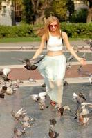 Smiling girl on park of Barcelona, running with pigeons photo